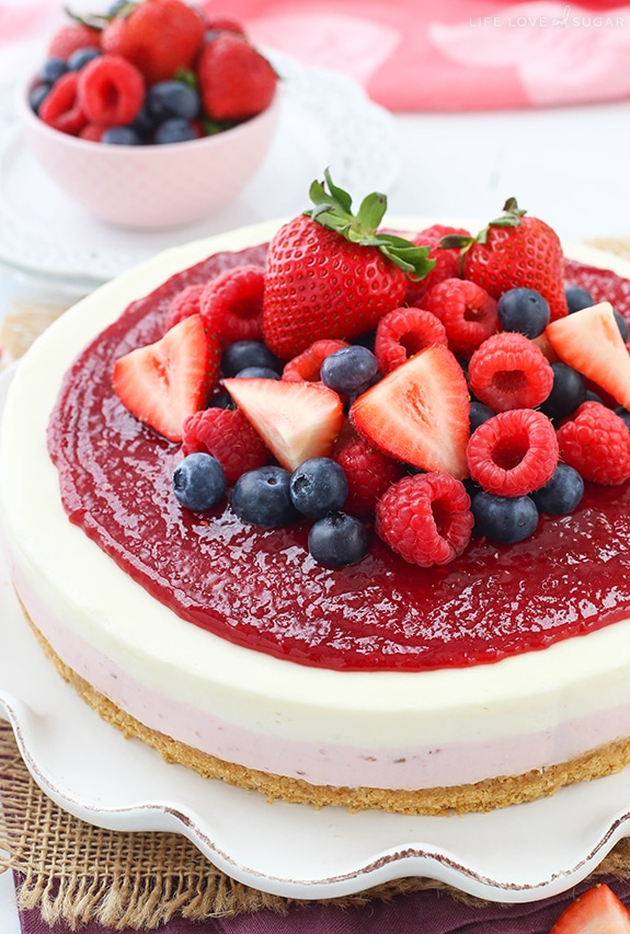 A No Bake Berry Vanilla Cheesecake topped with a layer of fruit spread and fresh strawberries, blueberries and raspberries