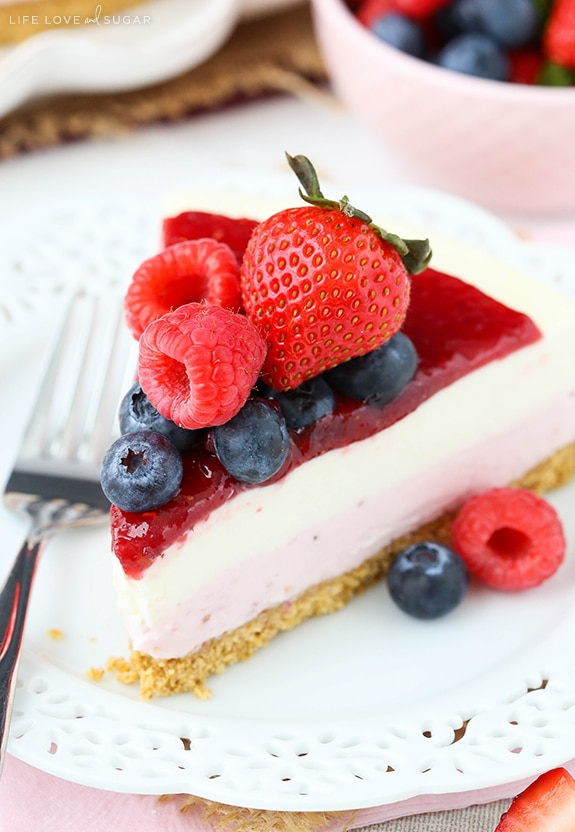 Close up of a slice of cheesecake topped with blueberries, raspberries and a strawberry on a plate