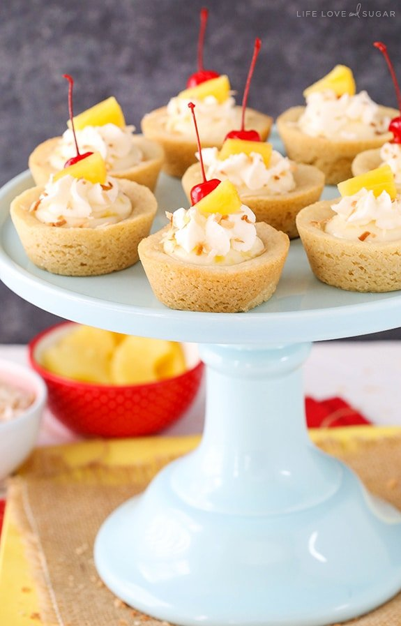Pina Colada Cookie Cups - a coconut cookie with pineapple cheesecake filling! The perfect summer dessert!