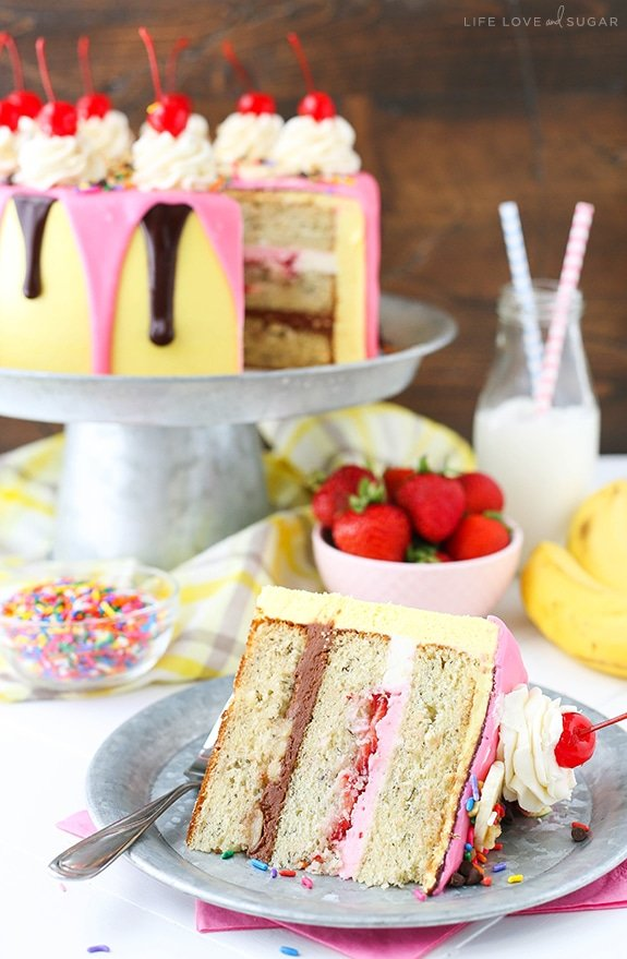 Banana Split Layer Cake - layers of moist banana cake with chocolate and strawberry buttercream filling, sliced bananas and strawberries, nuts, sprinkles and chocolate ganache! Banana split cake heaven!