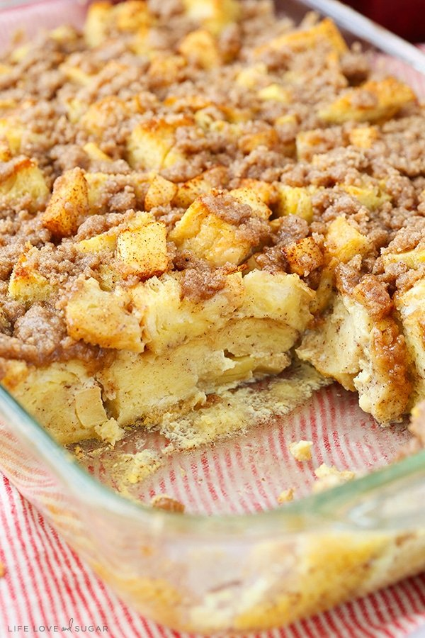 Apple French Toast Casserole with a serving missing in a glass baking pan