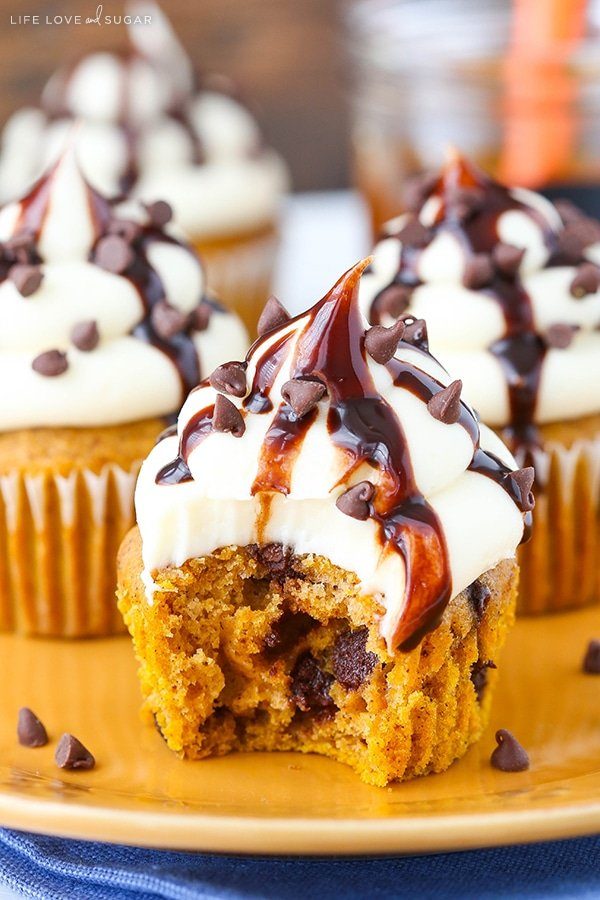 A pumpkin spice cupcake with chocolate chips and cream cheese frosting with a bite missing