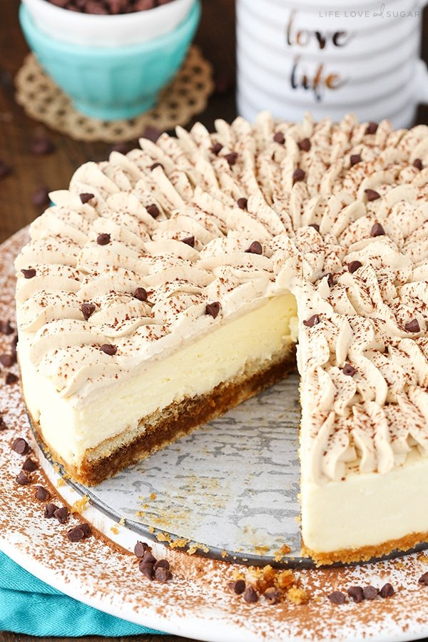 A tiramisu cheesecake with a slice taken out