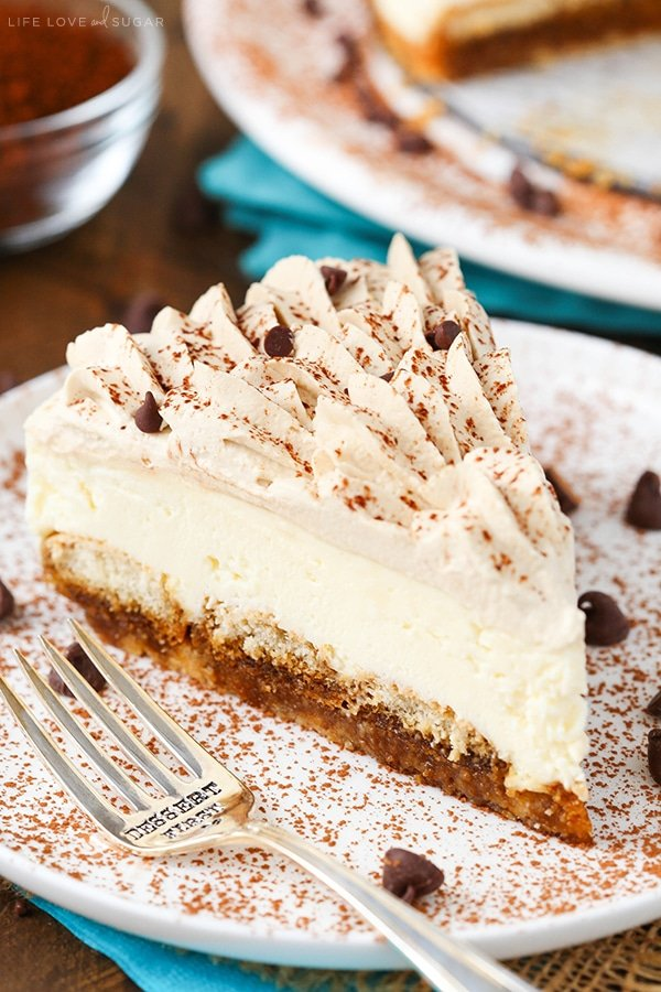 A slice of tiramisu cheesecake on a white plate with a fork