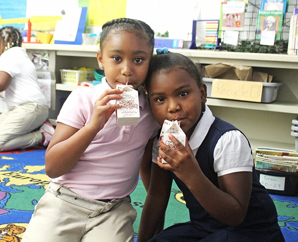 Two Girls Sipping From Their Milk Cartons Through Straws