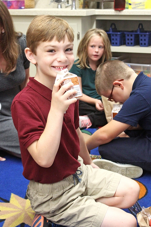 A Kid Drinking Milk Through a Straw and Smiling