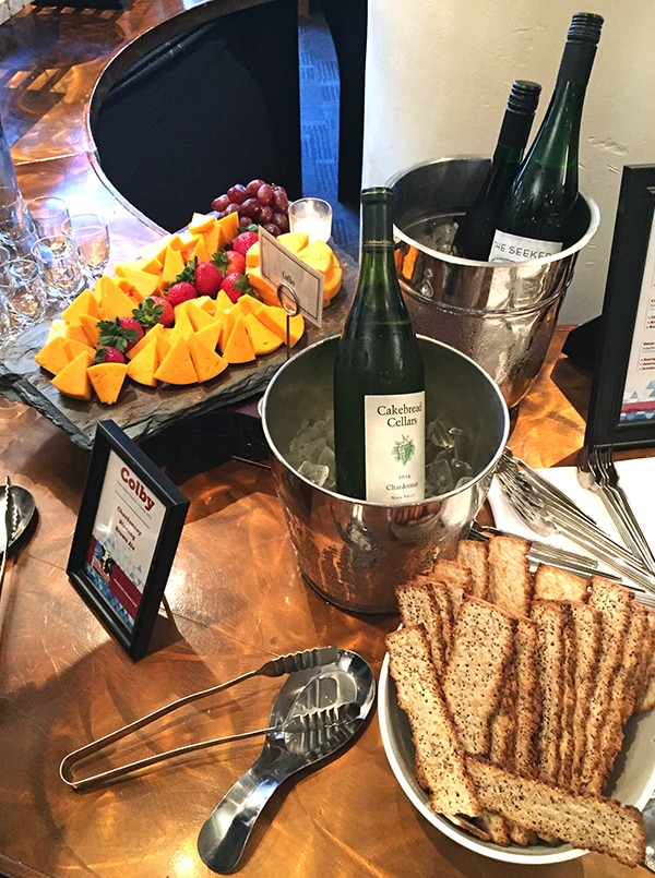 A Wooden Table Displaying Chilled Wine, Crackers, Cheese and Fruit