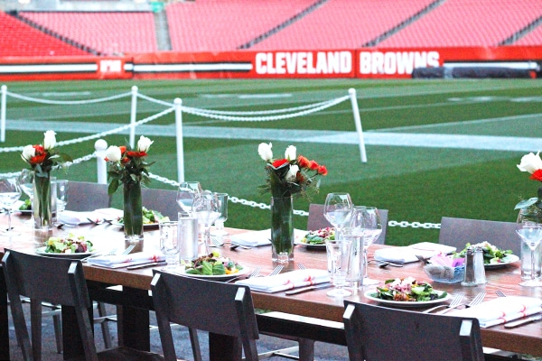 Our Tablescape at the Cleveland Browns Game with Vases of Red and White Flowers in the Center