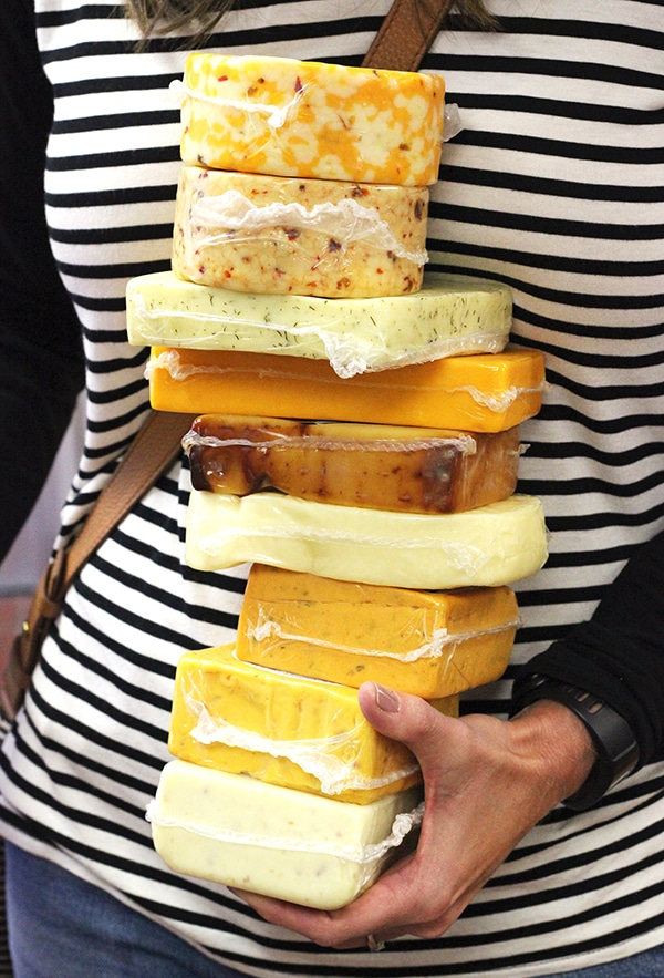 A Woman in a Black and White Striped Shirt Holding a Stack of Cheeses