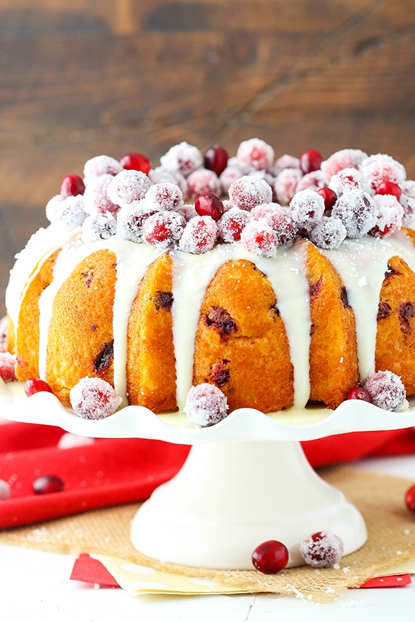 A bundt cake with sparkling cranberries and white chocolate ganache on top sits on a cake stand