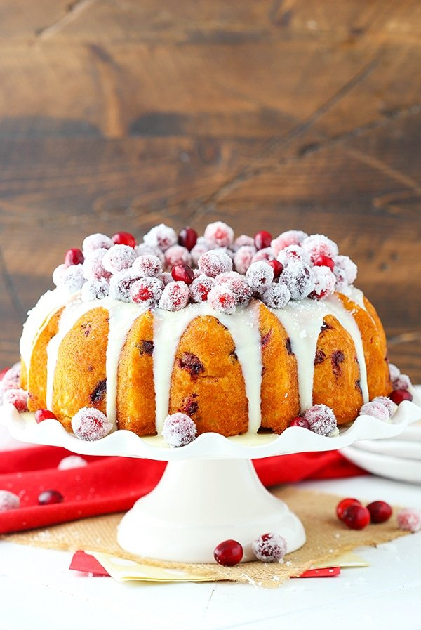 A bundt cake topped with sugared cranberries and ganache sits on a white cake stand