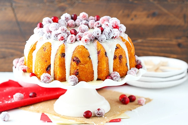 A whole Cranberry bundt cake with cranberries and white chocolate ganache on top sits on a white cake platter