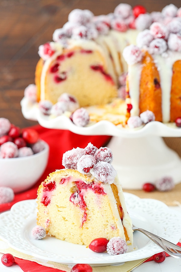 A slice of Cranberry White Chocolate Bundt Cake on top of a white plate and topped with sugared cranberries