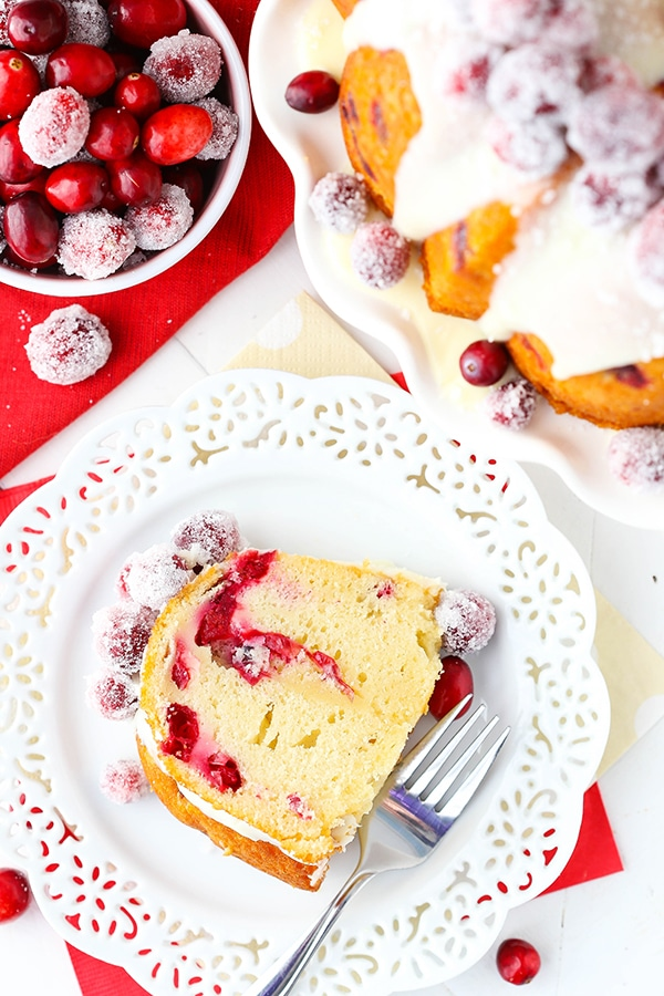 A slice of Cranberry White Chocolate Bundt Cake on a white lacy plate with a fork