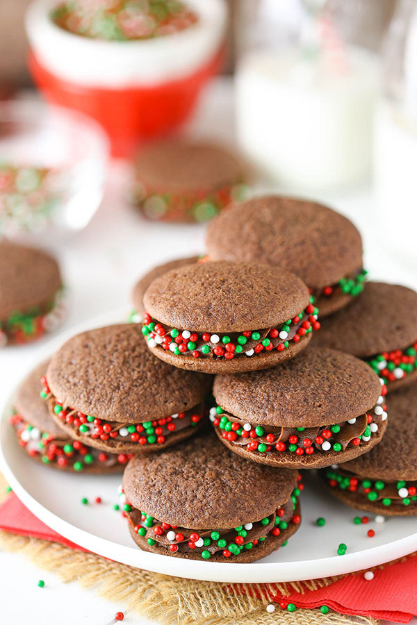 A bunch of Chocolate Cookie Sandwiches with sprinkles stacked on a white plate