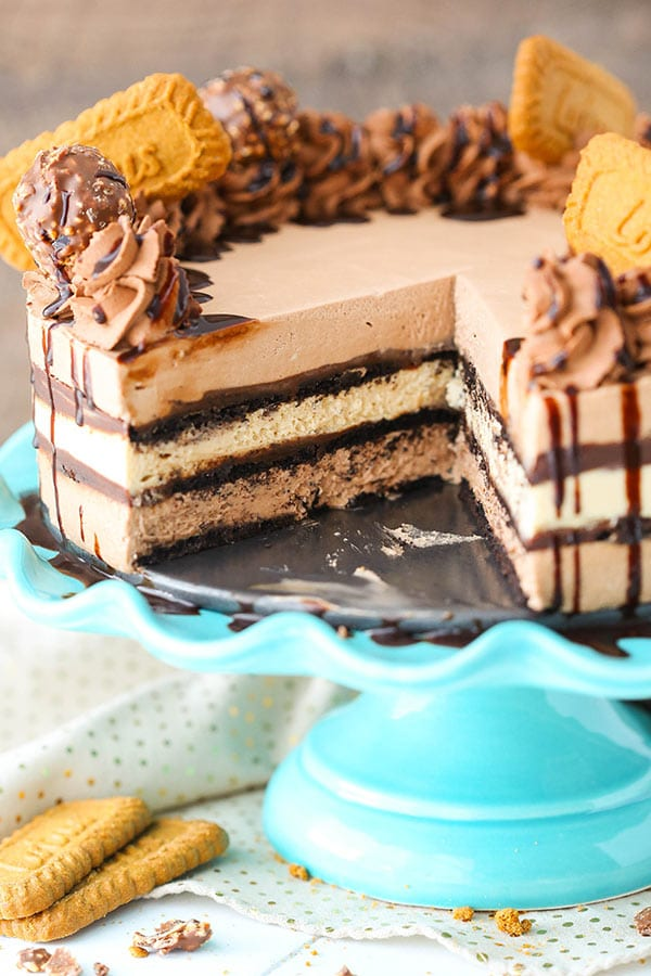 A Nutella Biscoff Icebox Cake with a slice missing exposing the layers of Nutella and Biscoff filling, and chocolate ganache