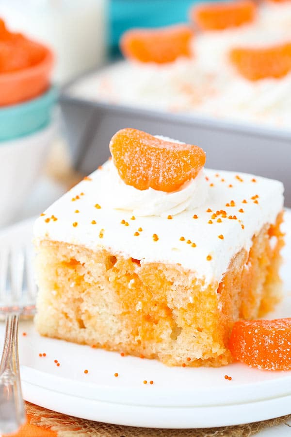 Image of a Slice of Orange Creamsicle Poke Cake on a Plate
