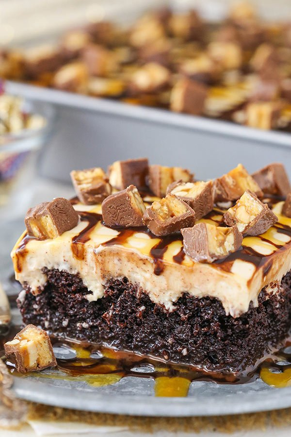 Snickers Poke Cake - chocolate cake soaked with caramel sauce and topped with peanut butter whipped cream!