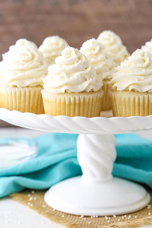 Moist and Fluffy Vanilla Cupcakes displayed on stand