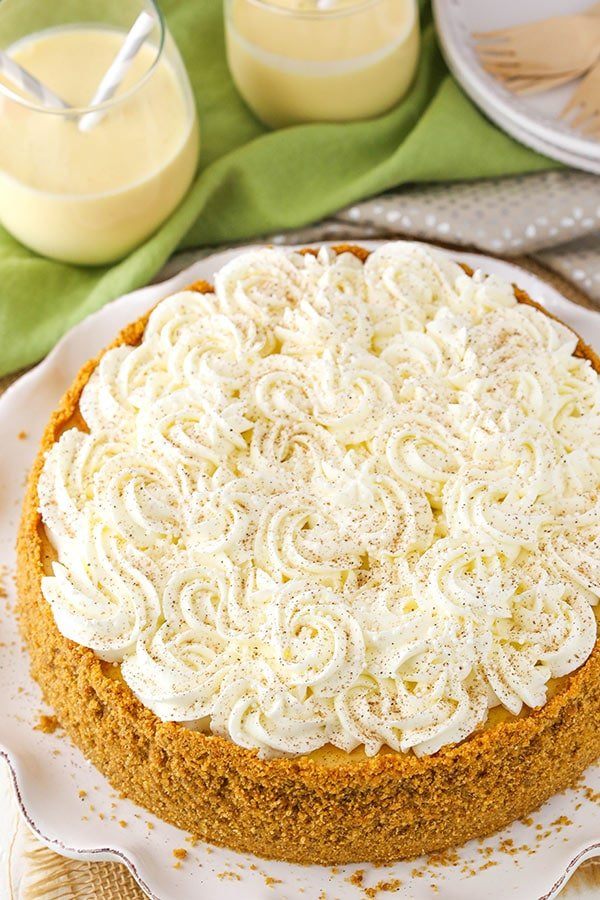 Eggnog cheesecake with swirls of whipped cream on top.