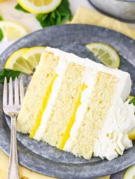 slice of lemon mascarpone cake on plate with lemon slices and mint
