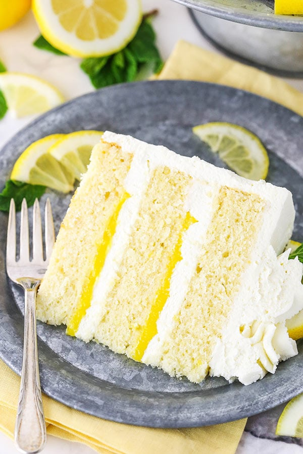 slice of lemon mascarpone cake on plate with lemon slices and mint