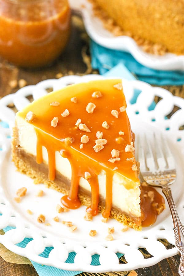 A slice of cheesecake covered in salted caramel and sprinkled with toffee bits