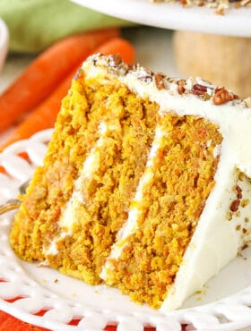 A slice of homemade carrot cake with cream cheese frosting on a white plate