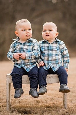twins on a bench in a field