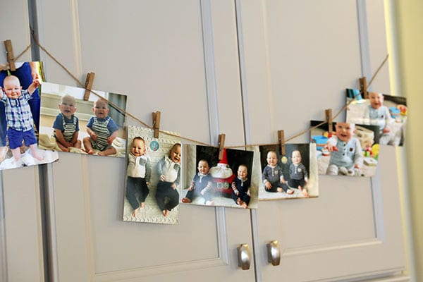 photos of twins first year clipped to twine