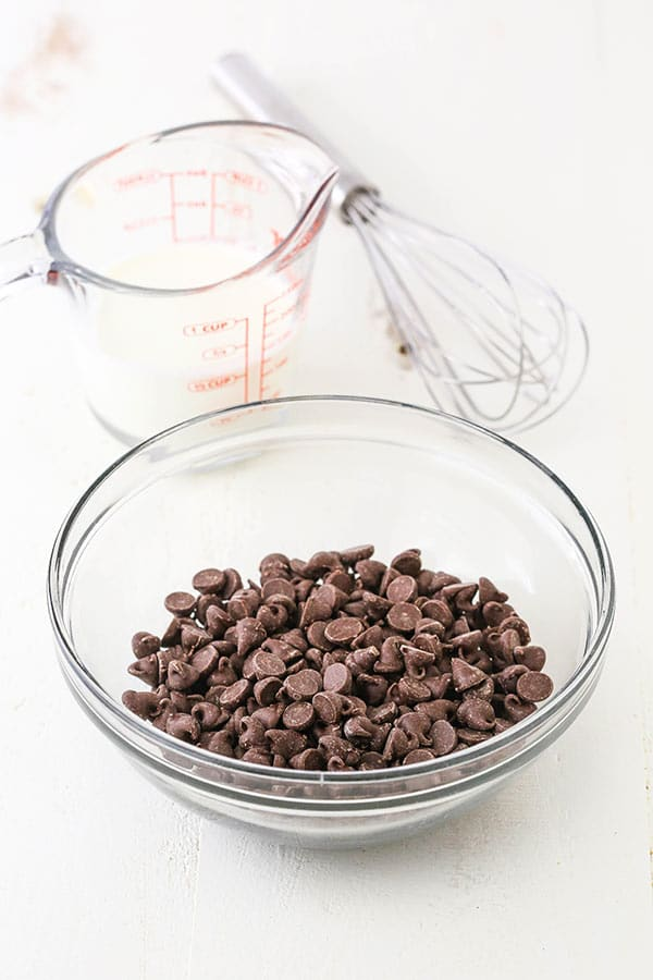 chocolate chips in a bowl with heavy cream in the background