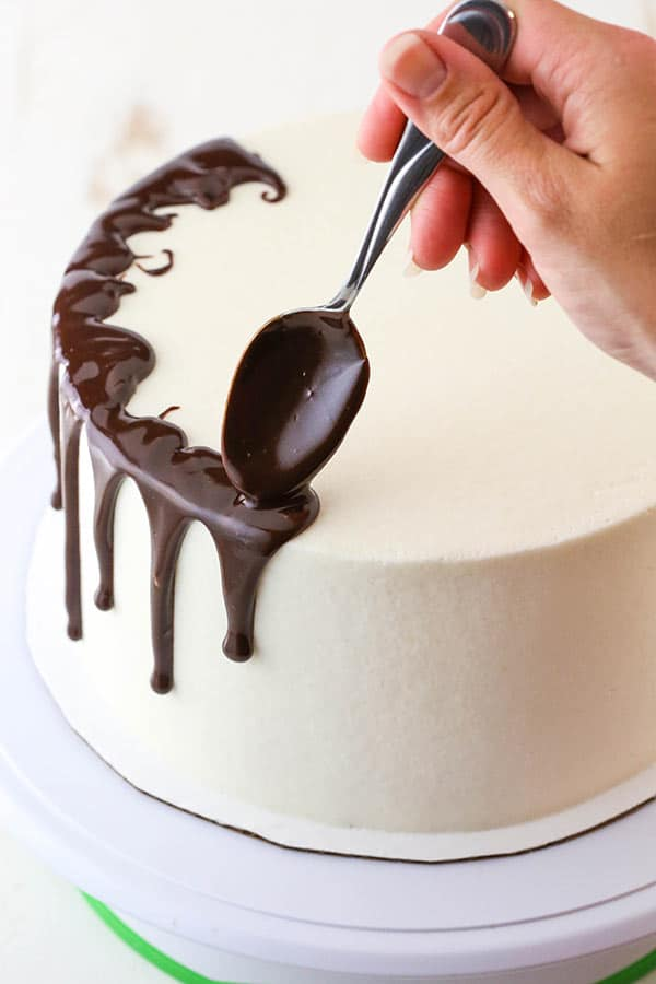 adding chocolate ganache to drip cake with a spoon