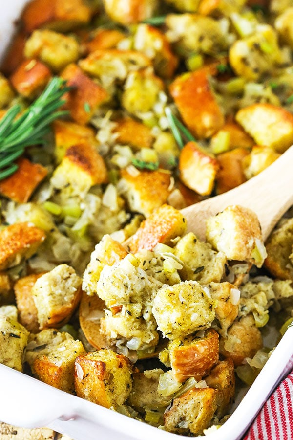 scooping homemade stuffing recipe out of a casserole dish