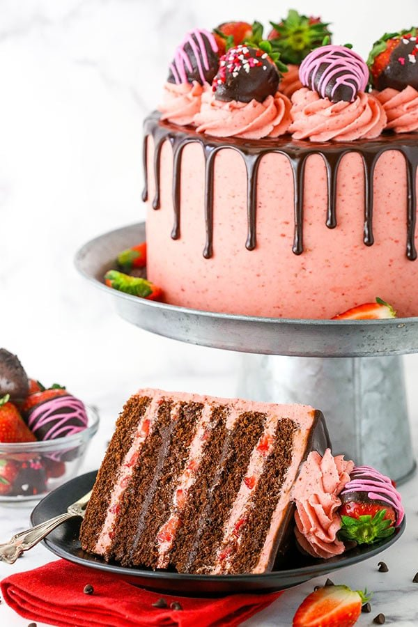 Chocolate Covered Strawberry Layer Cake slice on plate with cake on stand in background