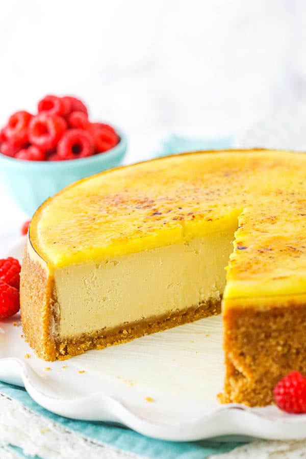 Creme Brûlée Cheesecake on white platter with slice removed