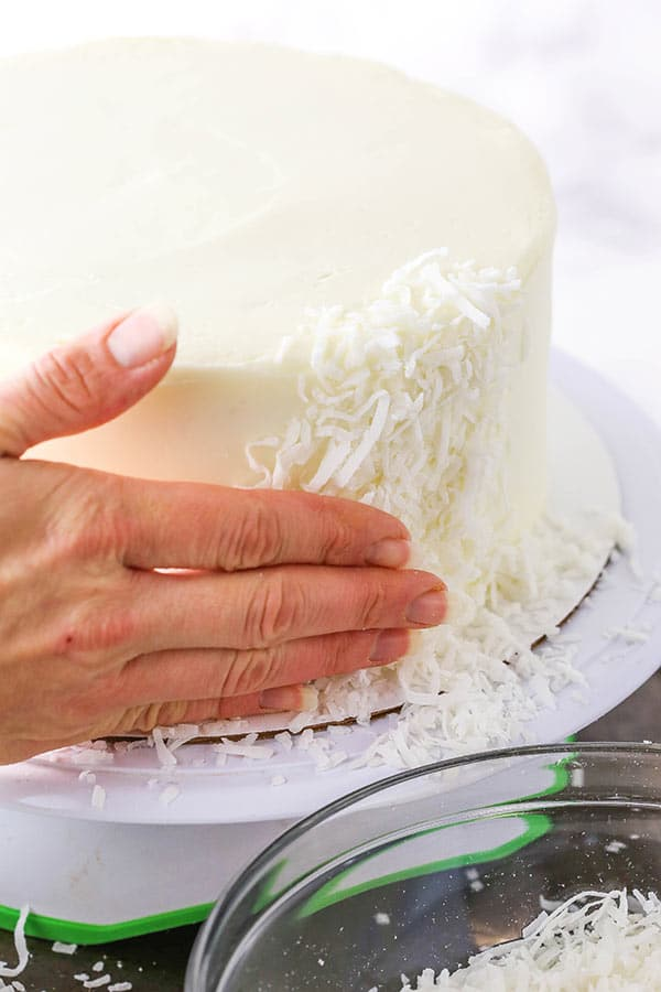 pressing coconut into side of cake