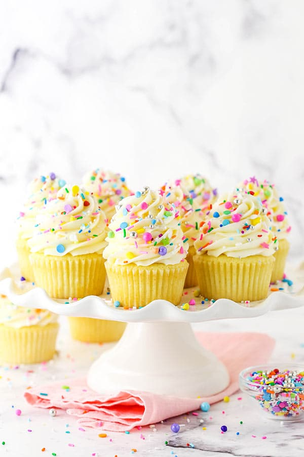 Homemade vanilla cupcakes with sprinkles on a white stand