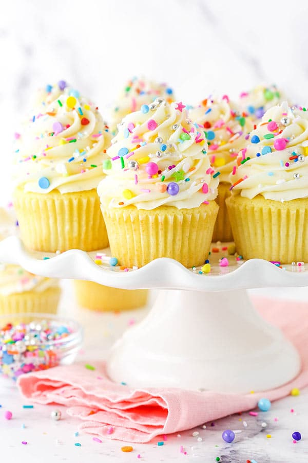 Frosted vanilla cupcakes on a cupcake stand with rainbow sprinkles