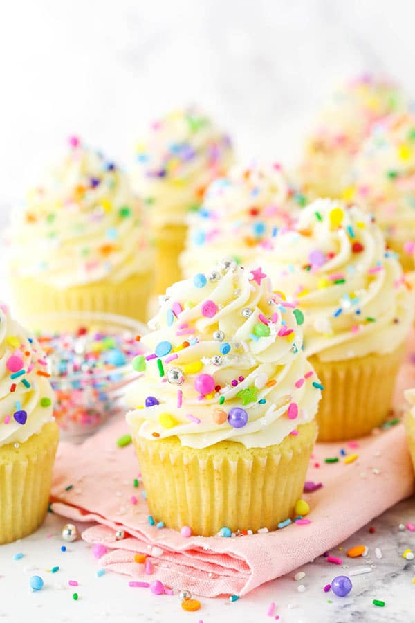 Close up of vanilla cupcakes with vanilla frosting and sprinkles