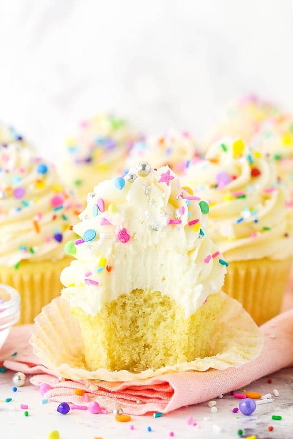Vanilla cupcake with frosting and sprinkles with a bite taken out of it