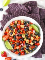 overhead image of berry fruit salsa in white bowl with blue tortilla chips