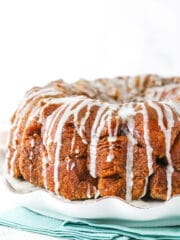 Side view of monkey bread with a glaze drizzle on a white plate.