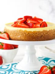 Side view of an instant pot cheesecake on a stand topped with sliced strawberries.