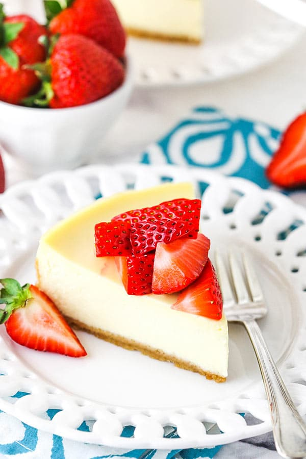 A slice of instant pot cheesecake on a white plate topped with strawberries