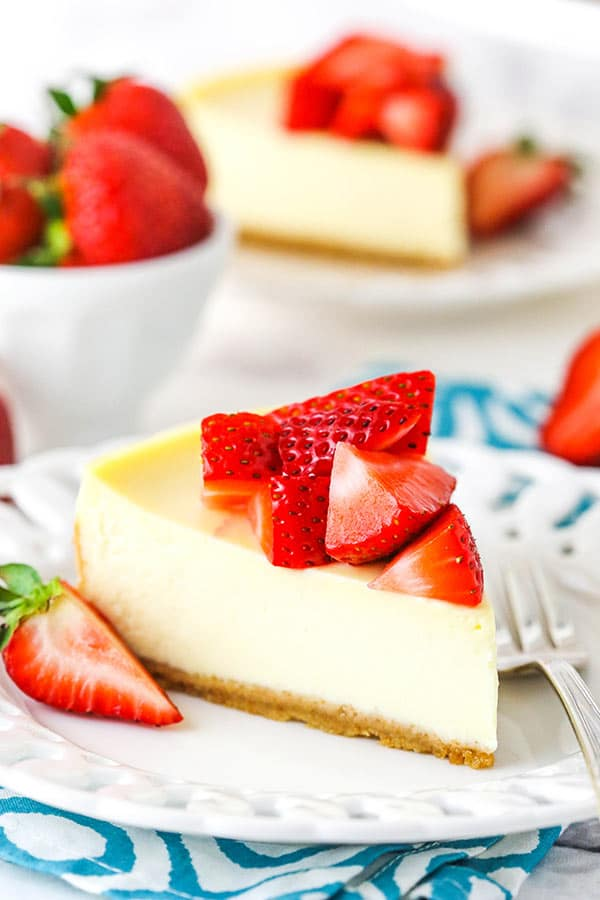 Side view showing a slice of cheesecake on a white plate topped with strawberries.