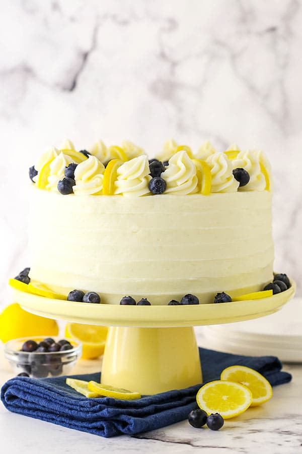 A frosted lemon blueberry layer cake on a pedestal.