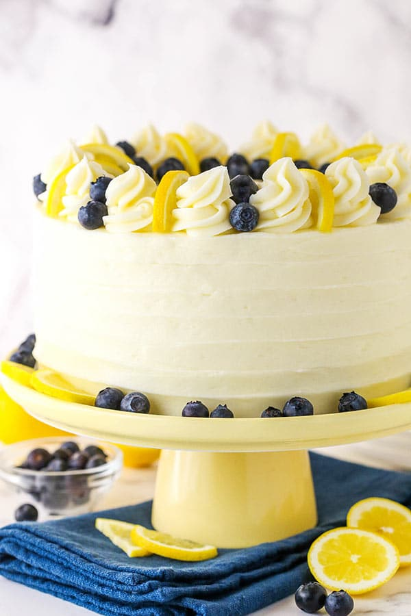Side view of a lemon blueberry cake on a cake stand.