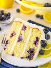 A slice of lemon cake dotted with fresh blueberries on a white plate.