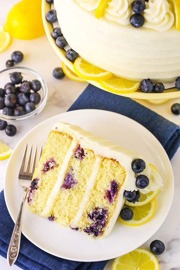 Top view showing a slice of cake surrounded by lemon slices and fresh blueberries.