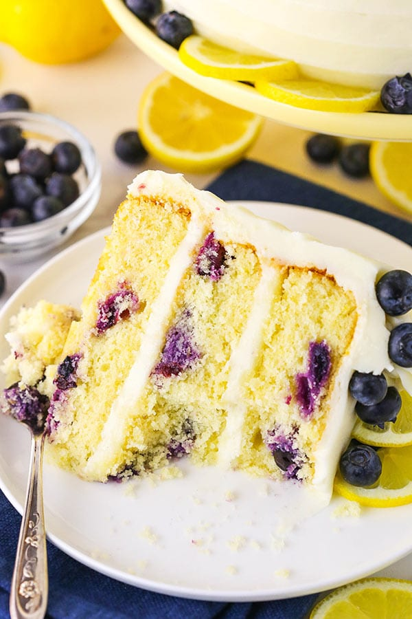 A slice of lemon blueberry cake on a white plate with a bite taken out of it.